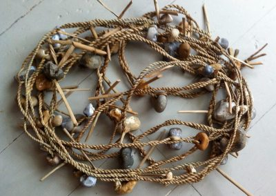 A photograph of a rush cordage with hagstones hand crafted by Christiane Gunzi