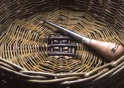 A photograph of a bodkin tool in a basket hand crafted by Christiane Gunzi